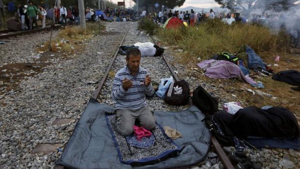 A Syrian refugee prays on a rail track at the Greek-Macedonian border. Photo: Yannis Behrakis via smh.com.au