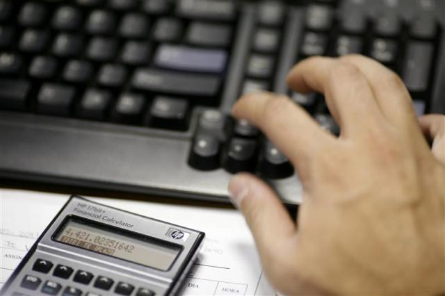 The hand of a broker is seen next to a calculator at Multiva Bank in Mexico City